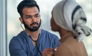 Male doctor with stethoscope checks heart rate of female patient wearing headscarf