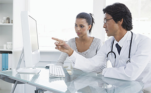 Stock image of a male doctor talking to a female patient while pointing at something on a computer screen