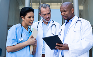 Stock image of three doctors reading off a tablet outside of a hospital building